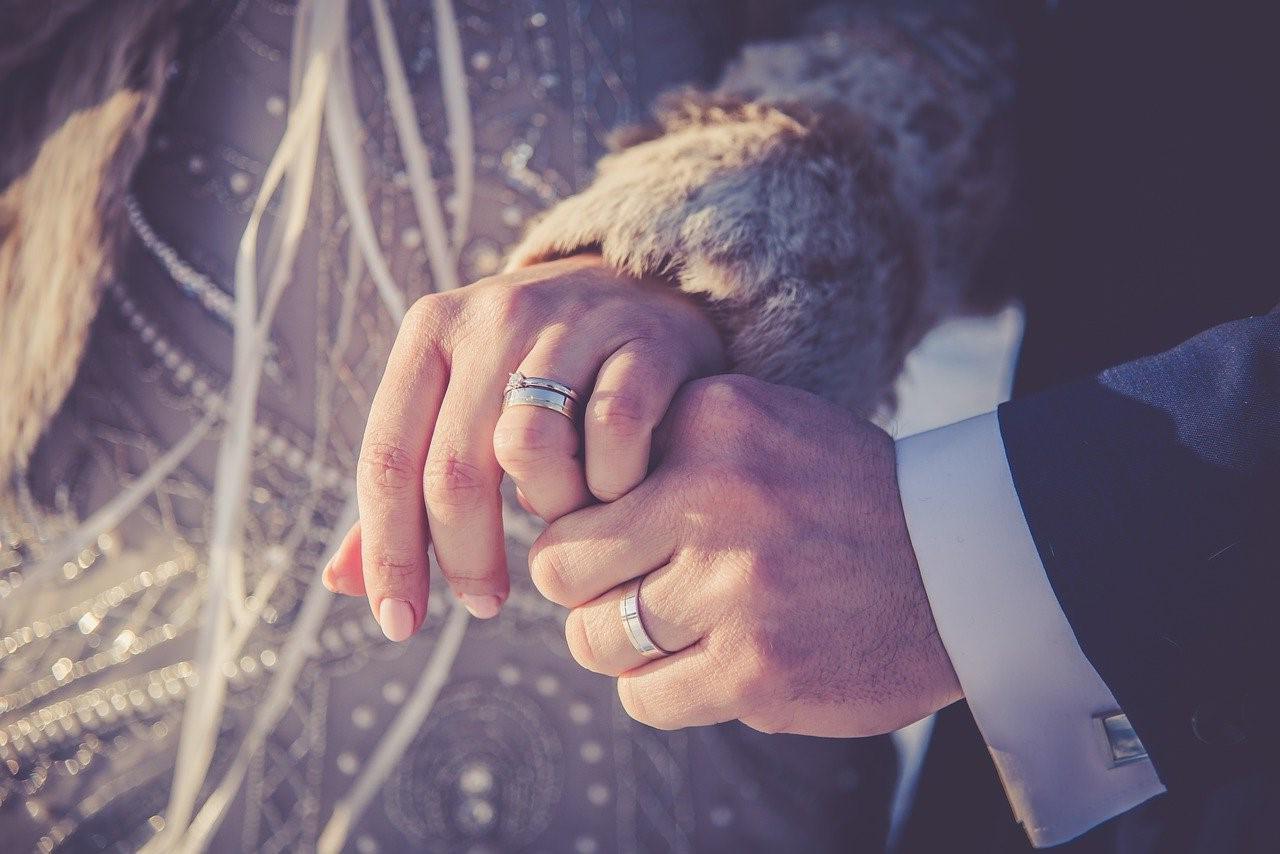 手を取り合うふたりの薬指に光る結婚指輪