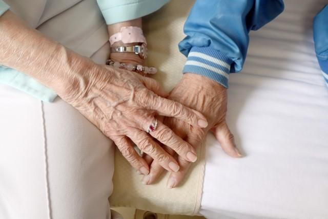手をつなぐ老夫婦の指に光るジュエリー