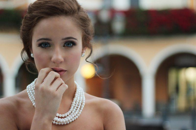 パールのネックレスを着けてこちらを見つめる女性