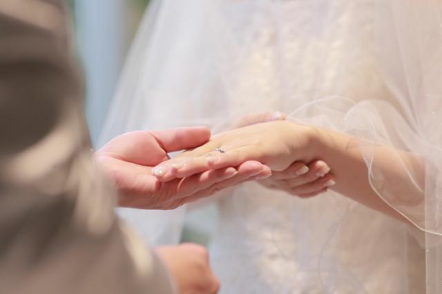 花嫁の薬指に結婚指輪をつける新郎