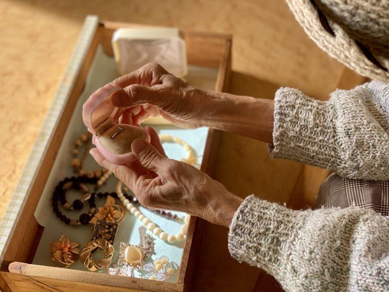 古いジュエリーを渡す老婦人の手