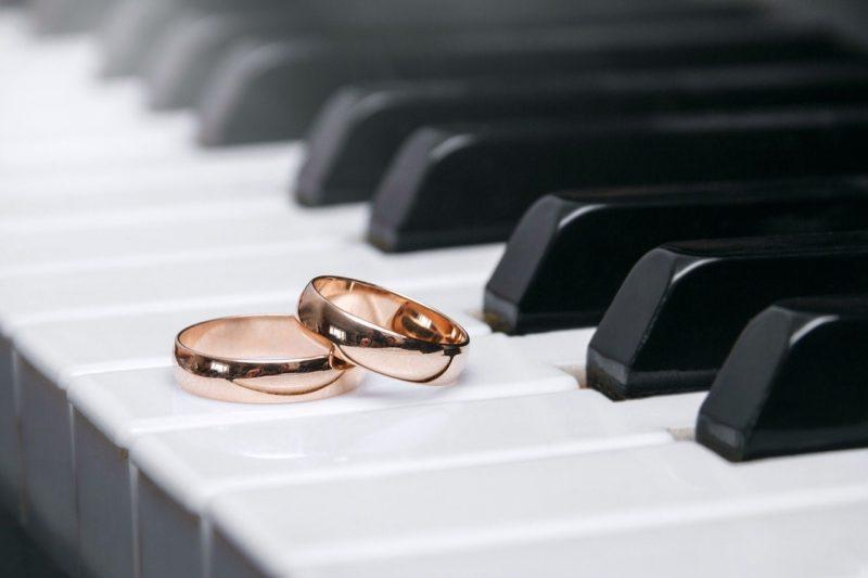 ピアノの鍵盤の上に置かれたピンクゴールドの結婚指輪