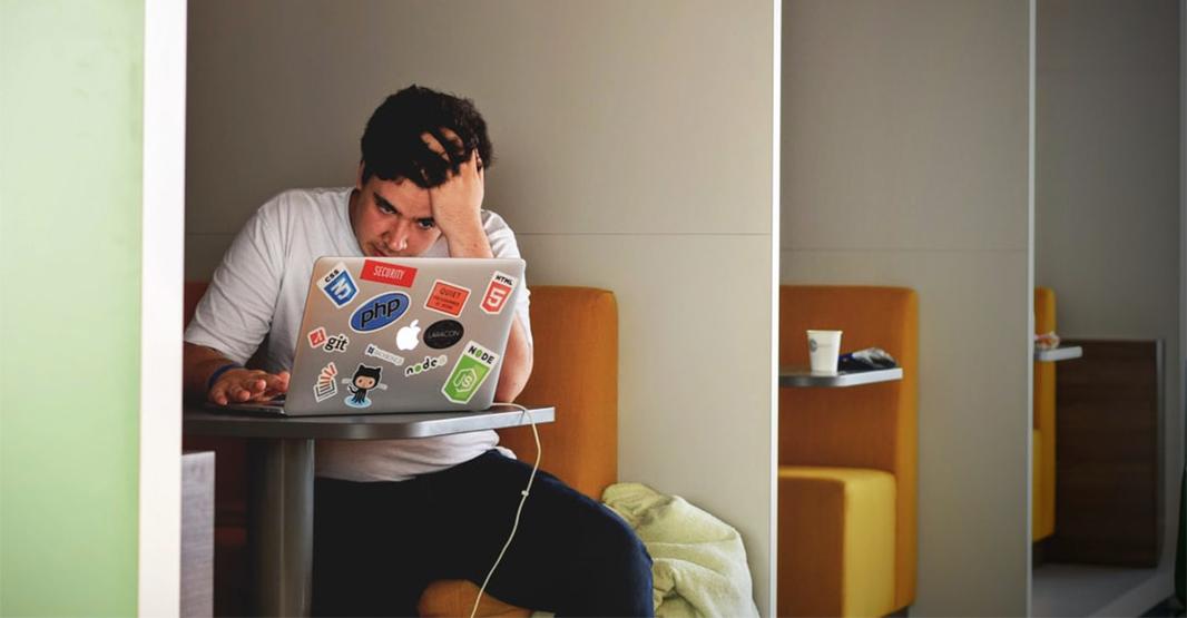 一人の男性がコーヒーショップのソファに座りパソコンを前に頭を悩ませている