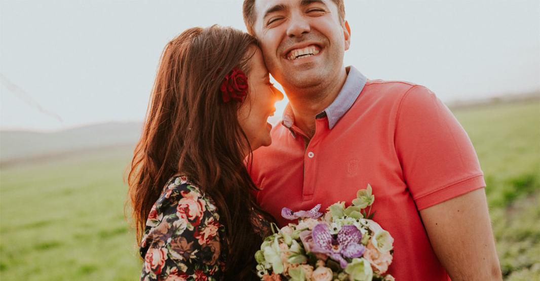 男性と女性が草原で笑顔で笑っている写真 女性は花束を持っていて幸せそうな表情