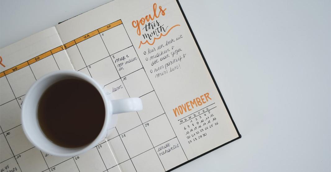 コーヒーとスケジュール帳が白い机の上に置かれている写真
