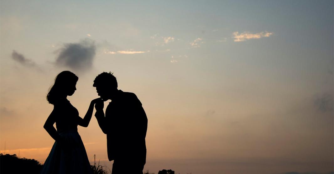 男性から女性にプロポーズ 夕日をバックにロマンティックな写真