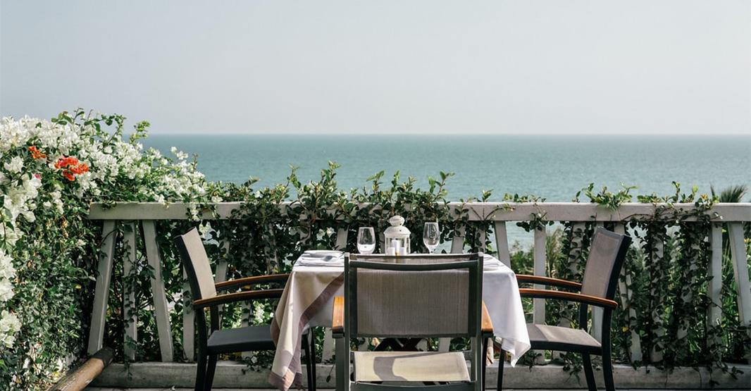海が見えるレストランの一席の写真 机の上にはグラスやプレートがセッティングされている。