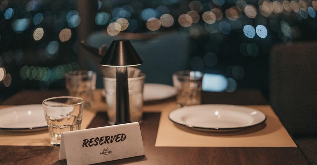 おしゃれなレストランのテーブル写真 テーブルの上には予約札とプレートがセッティングされている