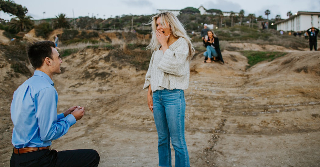 海沿いで男性が膝まづいて女性にプロポーズしている写真 女性はとても驚いている様子