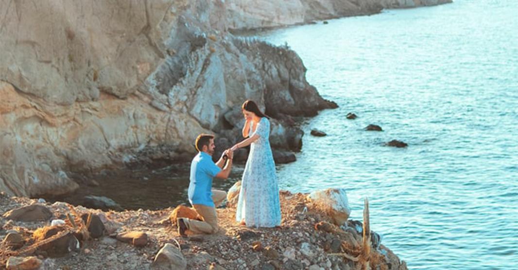 海辺で男性が女性に膝まづいてプロポーズをしている女性は驚いている様子
